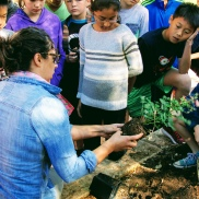 Dr. Kim Ballare showing students at an elementary school how to plant a pollinator garden. credit: Megan O'Connell
